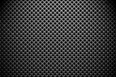diagonally: Braided diagonally oriented wire steel grid with reflections on black background under the wide spot light, abstract textured background