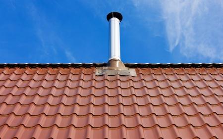 Rode pannendak met een tinnen schoorsteen onder de zon op een blauwe hemel achtergrond met witte wolken