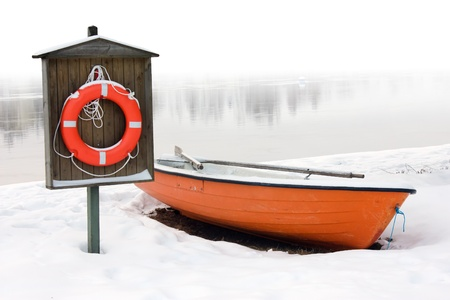 safety and lifesaving concept: orange lifeboat and orange lifebuoy on a snow-covered riverside in winter photo