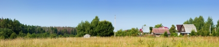 Wonderful summer panoramic view of the village and meadow photo