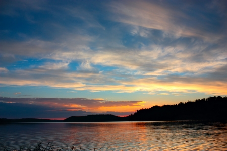Sunset on lake under blue sky, quiet evening landscape Stock Photo
