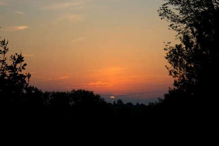 Sunset over trees in dark Stock Photo