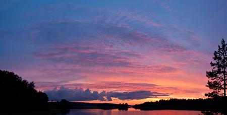 Bright red sunset over lake panorama