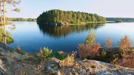Ladoga lake with island under summer sunset light panoramic view photo