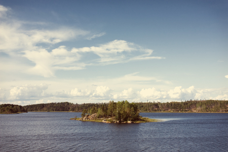Ladoga lake with small island under summer sunset light panoramic view. Toning effect done with a vintage retro Instagram style filter photo