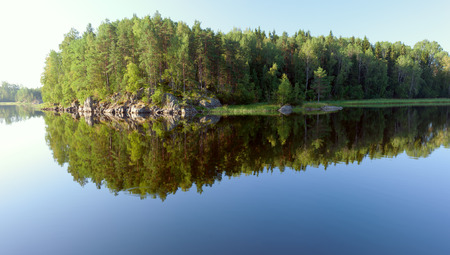 Island on Ladoga lake under summer sunset light panoramic view photo