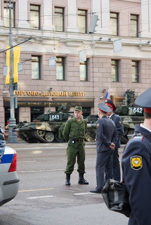 festivities: MOSCOW, RUSSIA - MAY 9, 2010: Police and military men near the T-90 tank prepared on Tverskaya street for parade festivities devoted to 65th anniversary of Victory Day on May 9, 2010 in Moscow.