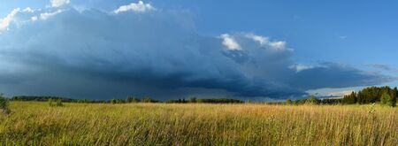 storm cloud: Panoramic landscape of meadow in countryside in sunset light and cloudy sky with big storm cloud before the storm Stock Photo