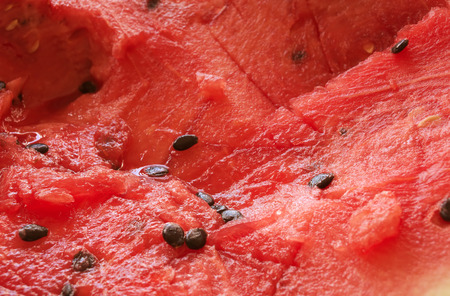 sliced watermelon: Natural healthy vegetarian foods fresh fruit background: red ripe watermelon chaotically sliced with watermelon seeds closeup view, photo with shallow depth of field Stock Photo