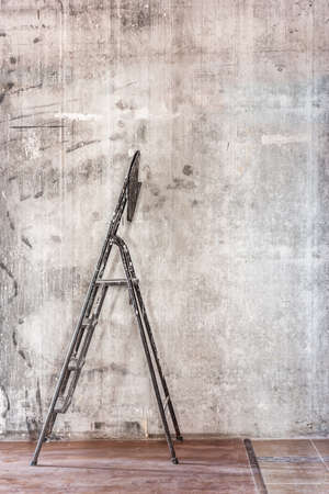 stepladder: Home interior room repair concept - old gray concrete wall and dirty brown floor in repairing room with old dirty black stepladder near the wall closeup view Stock Photo