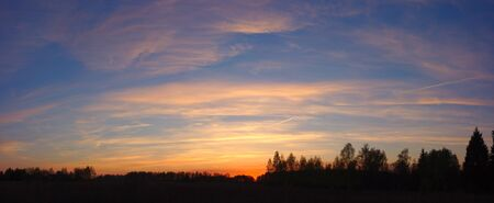 Sunset with clouds over silhouette of forest. Colorful panorama with blue sky, orange clouds and dark trees silhouette, natural background.
