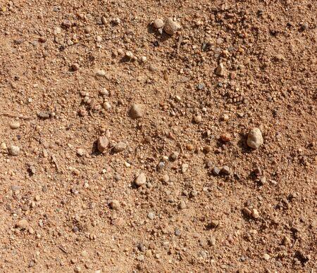 Ground textured surface background under bright sunlight, sandy soil close-up macro view 版權商用圖片