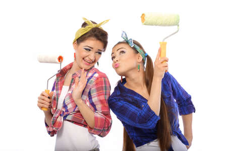 funy: Two fun girls are going to do painting walls.They are wearing funny clothes.In their hands they hold the rollers for painting walls.They dont know how to paint the walls and ceilings of the house.