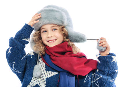 red scarf: Girl wearing winter fur hat.Portrait of a child dressed in winter hat and moms knitted warm sweater.On her neck she is wearing a dark red scarf and on his head a fur hat.