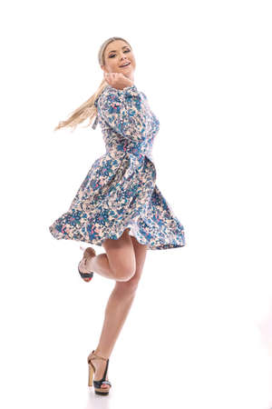 pies bailando: Long-haired blonde girl dancing in a beautiful blue dress.She is wearing a short summer dress with floral print.On his feet are shod with high-heeled sandals.Photos of dancing girl.
