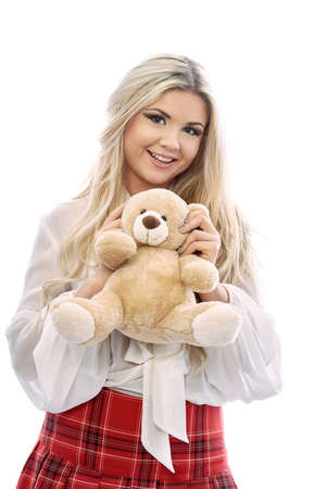 saturated color: Beautiful blonde plays with Teddy bear.The girl wears a Scottish skirt red saturated color and a white blouse.Girl kissing a toy.