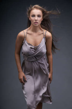 tight dress: Dark-haired girl in a tight dress resists the flow of the wind.Her hair blazing in the wind, the dress hugs tightly elastic body,and the posture shows the desire to break through the stream. Stock Photo