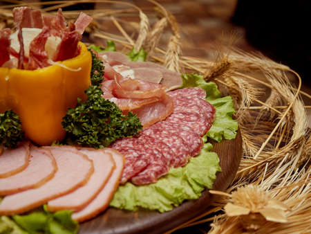 Different varieties of sausages and jerky meat lie on a plate. Stock Photo