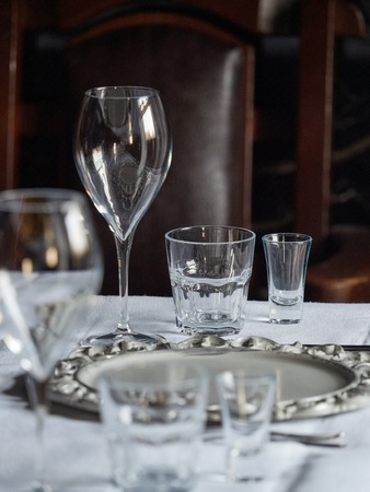 Various glass glasses are set on the table in the restaurant. Фото со стока