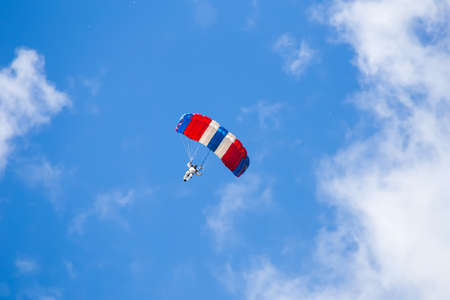 skydiver descends to earth in the clouds and blue sky view from the ground Stock Photo