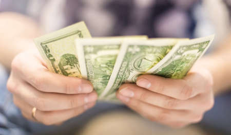 male hands holding dollar bills on a blurred background