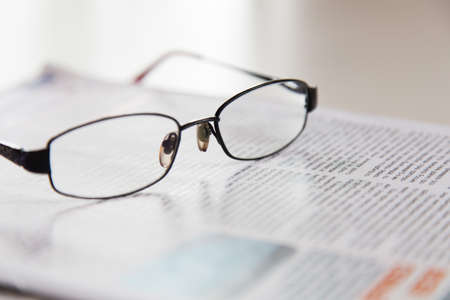 glasses on a daily newspaper.