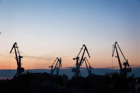 silhouettes of cranes on the extraction of river sand in a quarry against the backdrop of the sunset
