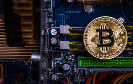 gold coin bitcoin on the motherboard among computer components Stock Photo