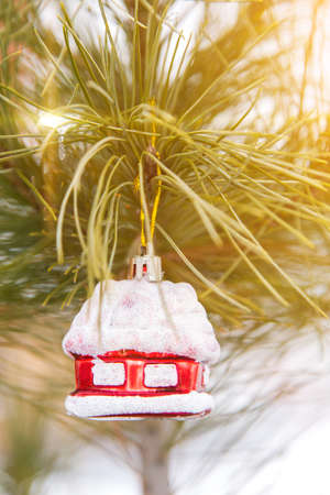 dwelling: Toy snow-covered house. Christmas tree toy. Brilliant Glass House. New Year. Stock Photo