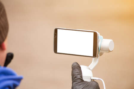 the person shoots on the phone with an electronic portable stabilizer. Close-up. screen smartphone for mockup. Imagens