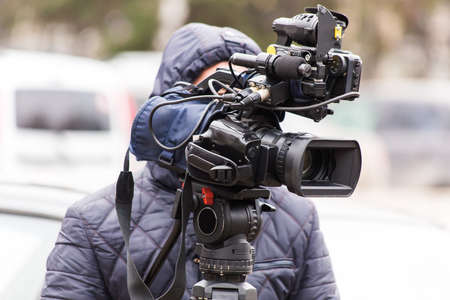카메라맨은 삼각대에서 전문가 용 비디오 카메라에 대한 보고서를 작성합니다. 거리 보고서.