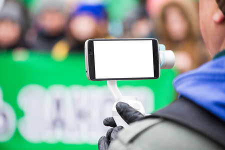 the person shoots on the phone with an electronic portable stabilizer. Close-up. screen smartphone for mockup. Stock Photo
