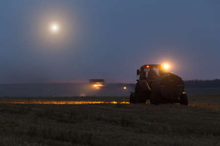 night harvesting in the fields. night harvesting in the fields. tractor with additional fuel. Stock Photo