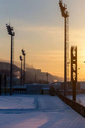 Mast Beleuchtung Mäntel im Stadion auf einem Sonnenuntergang Hintergrund.