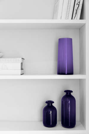 black and white photo of home interior design. closet shelves with vases and books closeup in colors of the year 2018 Ultra Violet pantone. 免版税图像