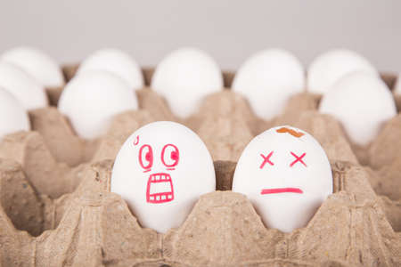 concept. two eggs among the rest in the package. an egg with a smile of horror looks at the broken egg.