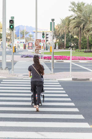 A young woman with a stroller crosses the road on a pedestrian crossing. back view Stock Photo