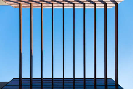 geometry in architecture. Vertical beams connecting the walls against the blue sky