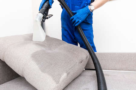 Cleaning service. Man janitor in gloves and uniform vacuum clean sofa with professional equipment. Archivio Fotografico