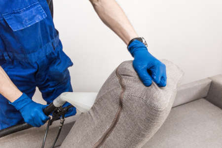 Cleaning service. Man janitor in gloves and uniform vacuum clean sofa with professional equipment. Stock Photo