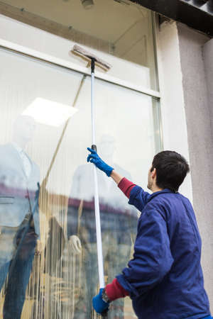 A young male cleaner in blue overalls washes windows and store front. Cleaning Service