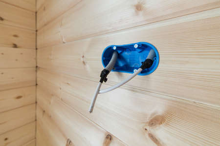 A blue hood in the wall for an outlet or switch with a protruding insulated wire. Electric wiring in a wooden house 版權商用圖片