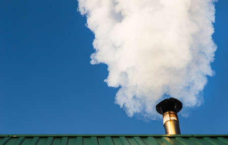 Smoke comes from the chimney of the house against the blue sky. The pipe on the roof. Chimney. Country house.