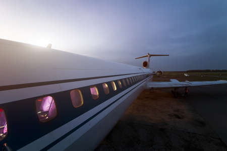 The fuselage and iluminators of a passenger airplane close-up against a darkening sky Imagens
