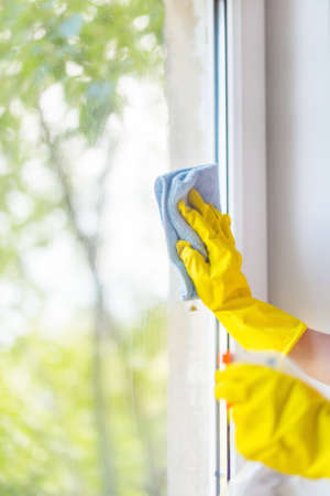 A female hand in bright yellow rubber gloves washes. cleaning the window with a soft rag. Nice view from the window Stock Photo