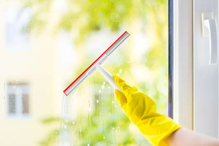 hand cleaning glass window pane with detergent and rubber aluminum wiper. A female hands in bright yellow gloves washes the windows
