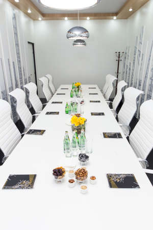 Ufa, Russia 24 May 2018: Business Forum - Oil and Technology.Bottles of water, glasses and snakes on the white empty meeting table and with white chairs. Business concept Editöryel