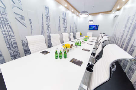Ufa, Russia 24 May 2018: Business Forum - Oil and Technology. Bottles of water, glasses and snakes on the white empty meeting table and with white chairs. Business concept
