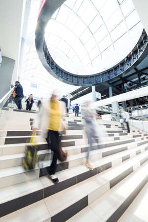 Ufa, Russia 24 May 2018: Business Forum - Oil and Technology. People go down and climb the stairs in a public place. Photo in motion on long exposure