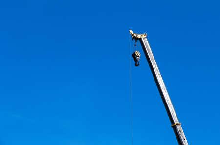 Arrow of a crane with a hook on a blue sky background